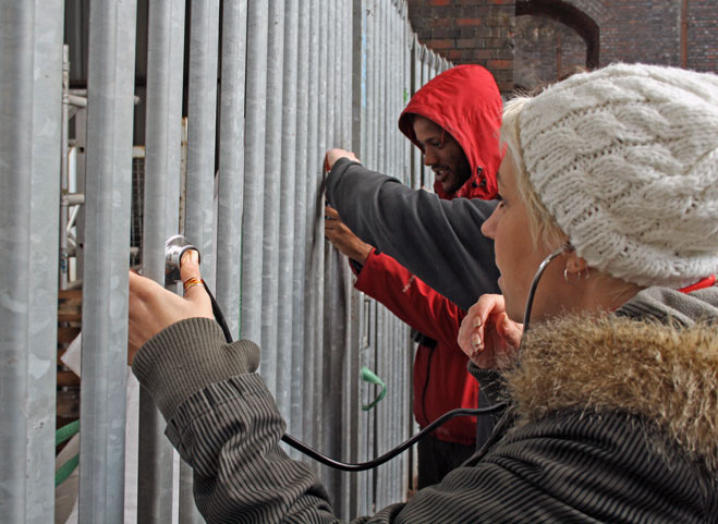 Listening to a metal fence with a stethoscope