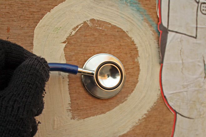 Listening to a wooden board with a stethoscope